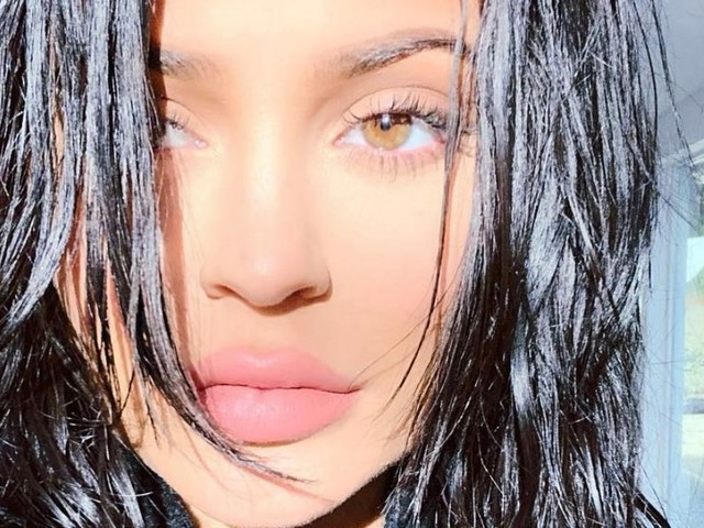 Kylie Jenner posts string of sultry selfies but keeps her 'baby bump' covered up under baggy jumper