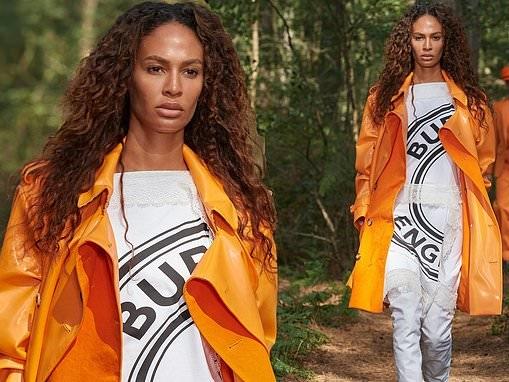 Joan Smalls flaunts her model figure in bright orange trench coat