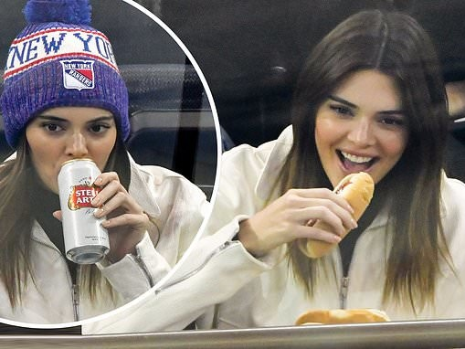 Kendall Jenner tucks into FOUR hot dogs and swigs cans of Stella at Rangers