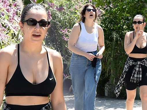 Charli XCX wears a busty sports bra as she steps out with a friend