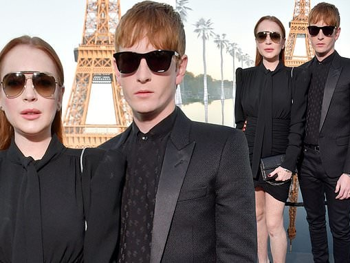 Lindsay Lohan is super chic in black mini skirt and tie as she hits the FROW forYves Saint Laurent