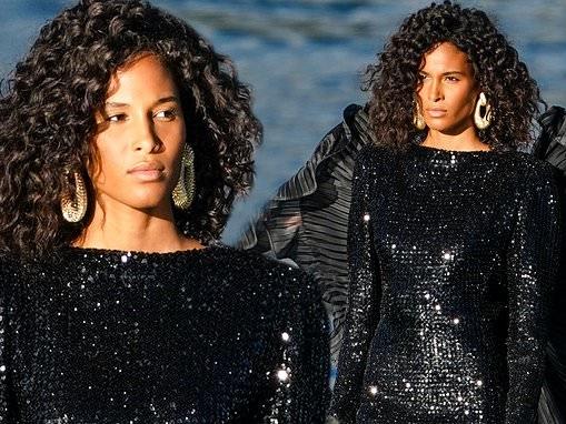 Cindy Bruna dazzles in a glitzy black maxi dress during the Balmain Sur Seine fashion show