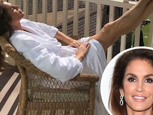 Cindy Crawford flashes her toned legs in bathrobe