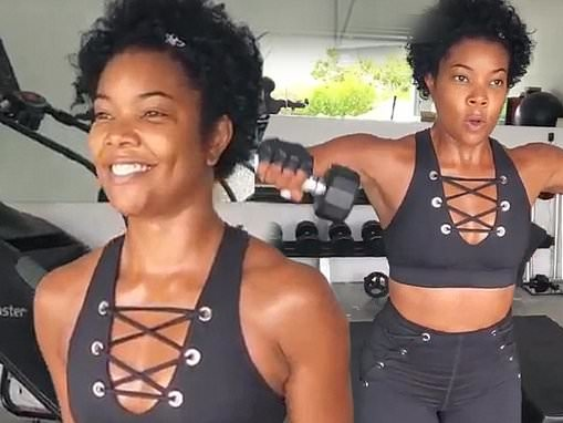 Gabrielle Union shows off her taut midriff in laced-up black activewear as she works out in home gym