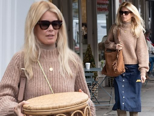 Claudia Schiffer cuts a chic figure in a beige chunky knit jumper and denim midi in Notting Hill