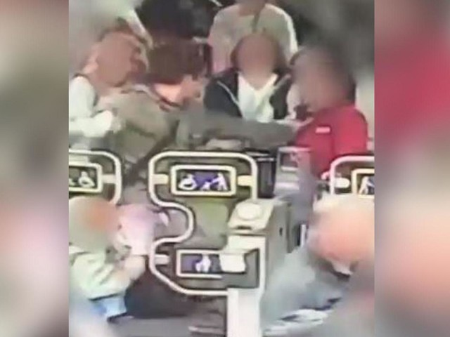 Police hunting thug who punched female ticket guard in face after lifting child over barrier in Manchester