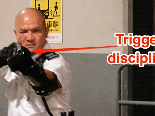 Hong Kong police officer makes a grave safety error waving a shotgun in protesters' faces