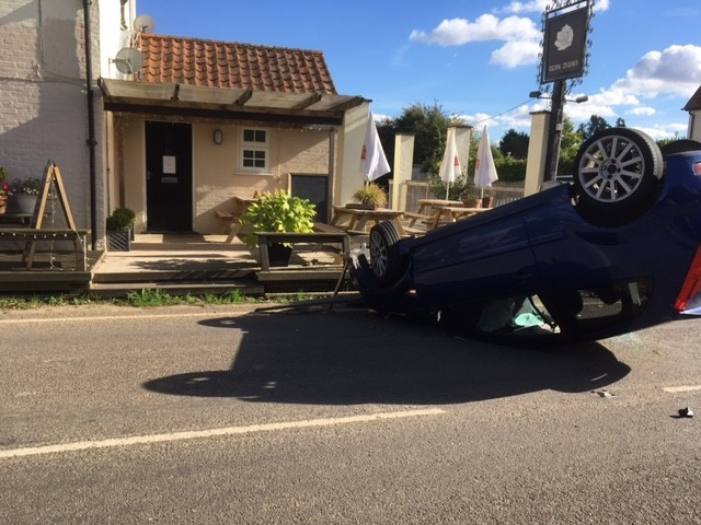 Driver's lucky escape as car flips outside pub