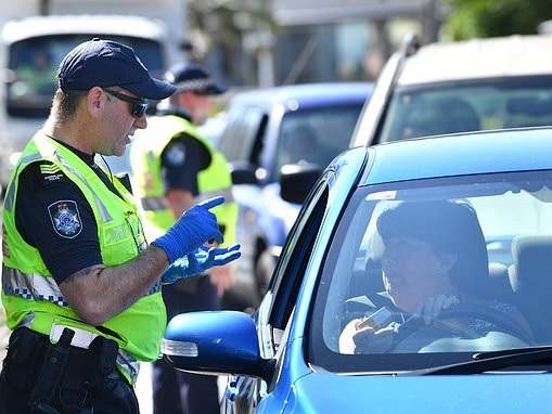 Couple sitting in a car in a suburban street are fined $2,000 under strict new coronavirus laws