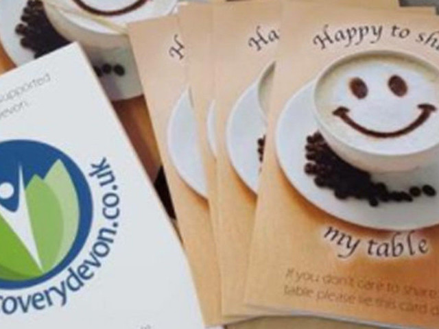Former Carer Tackles Loneliness By Planting 'Happy To Share' Table Cards In Cafés Across Devon