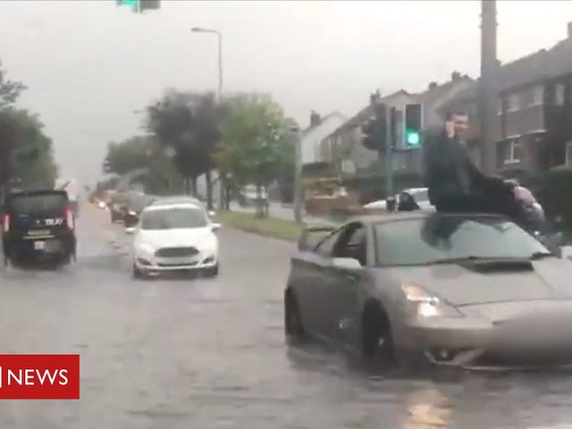 Edinburgh flooding: Man sits on top of car