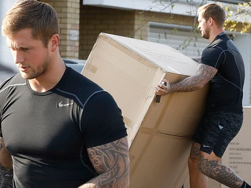 Dan Osborne shows off his muscles as he hauls boxes into his house