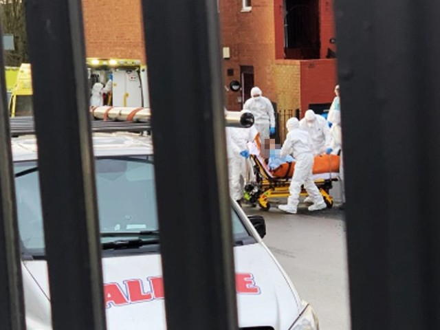 Police and paramedics in white suits descend on house after woman found with life-threatening injuries