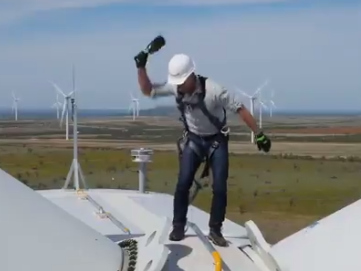 Jeff Bezos smashes a bottle of champagne while perched on top of a giant wind mill