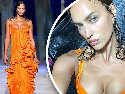 Irina Shayk takes a break from the catwalk at MFW and puts on busty display in plunging orange gown