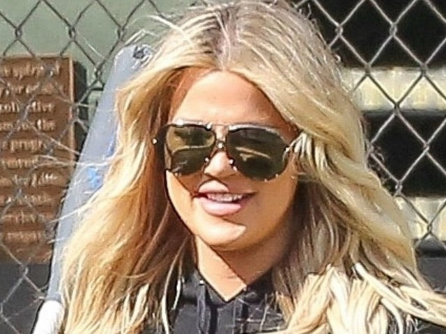 Pregnant Khloe Kardashian cradles 7 month baby bump as she plays baseball with mum Kris Jenner and sister Kim