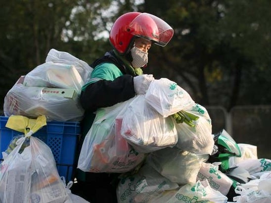 Photo shows an extraordinarily overloaded Chinese worker delivering massive amounts of food because no one wants to go outside and risk catching coronavirus