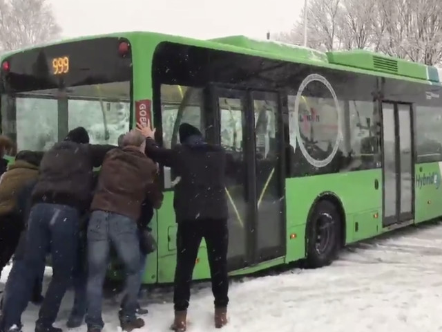 Watching strangers help push a bus stuck in the snow will put you in the Christmas spirit