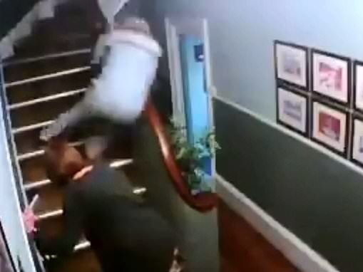 Drunk couple caught on camera falling down B&B stairs with drinks in hand