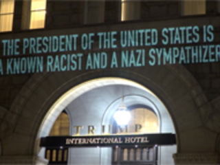 Protestor armed with a projector takes aim at Trump Hotel: VIDEO