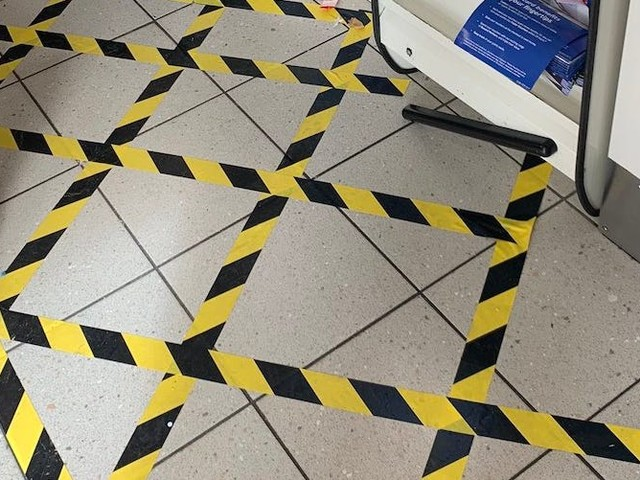 The UK's largest grocery store chain instructs shoppers to stand behind a taped area at checkout to prevent the spread of the coronavirus