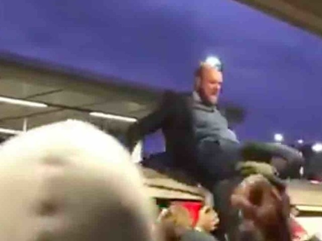 Climate change activist stands atop London train, infuriating delayed commuters. So they drag him off the roof.