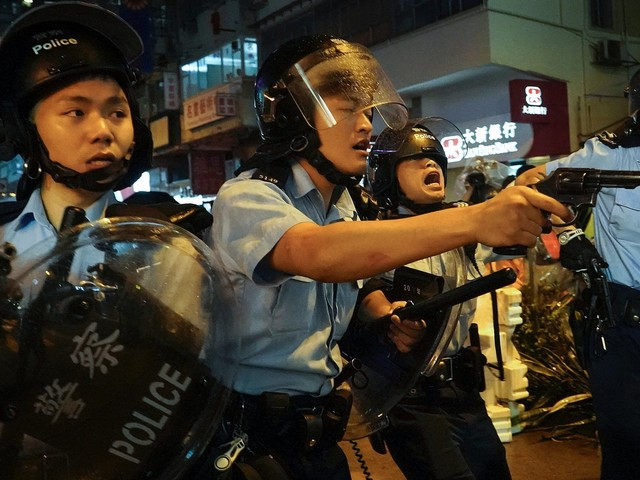 Hong Kong police drew their guns and fired a warning shot after being chased by protesters