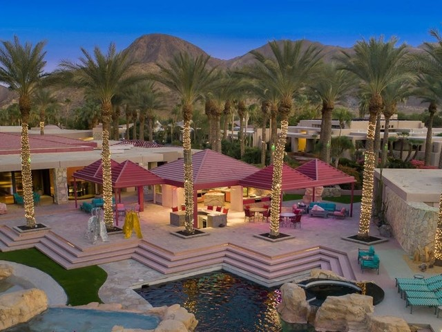 A very pink 1980s mansion in an exclusive desert enclave near LA comes with neon light fixtures and a waterfall bar. Take a look inside.