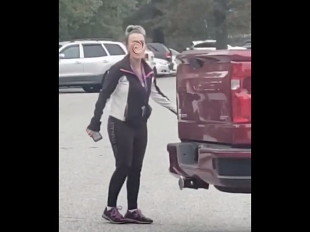 Teacher is suspended after she loses it on a parent during racist rant in school parking lot. The ugly interaction is caught on video.