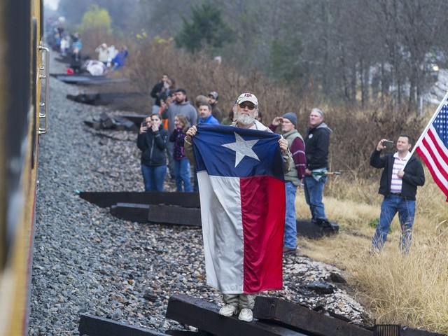 Thousands line train tracks to watch Bush funeral train to College Station