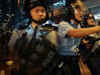 The Latest: HK police draw guns as protesters chase them