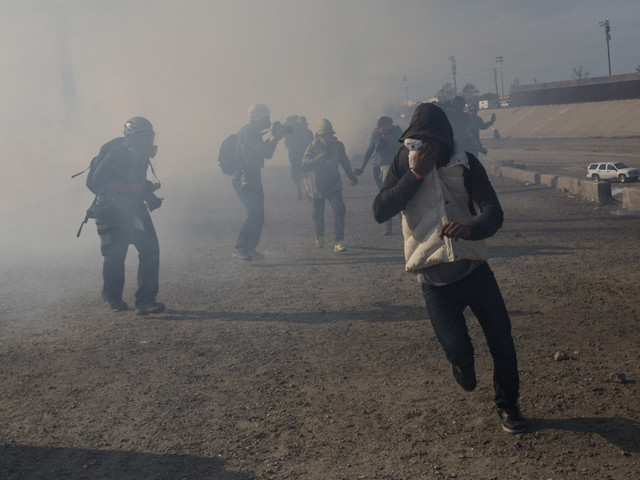US agents fire tear gas as some migrants try to breach fence