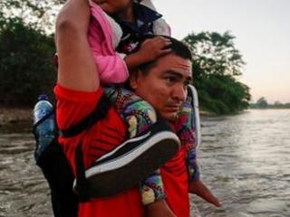 Migrant caravan crosses into Mexico, walks along highway