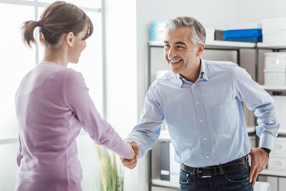 Frau und Mann schütteln Hände über Vertragsabschluss – Arbeitsvertrag erstellen
