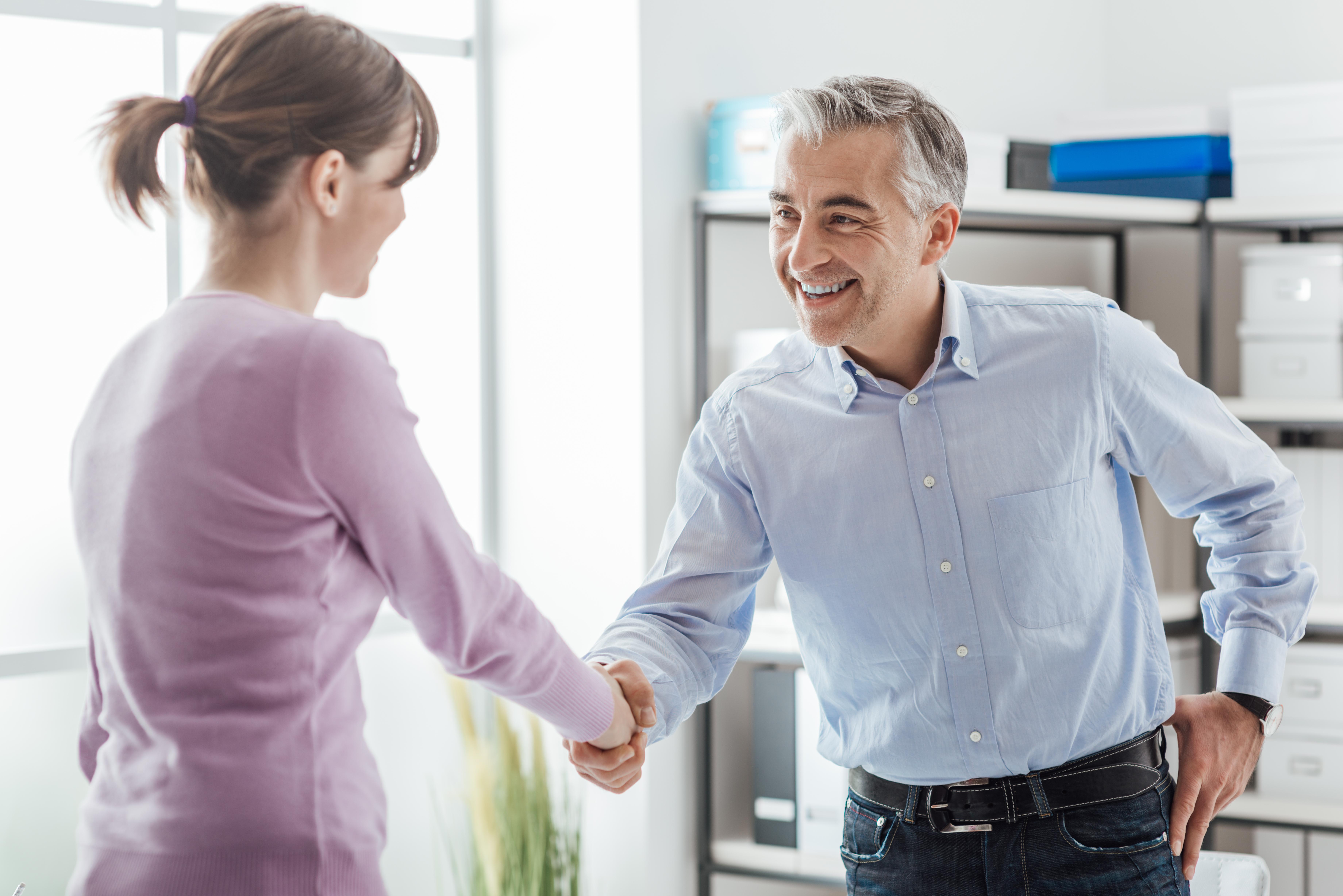 attraktiver Arbeitgeber schüttelt Bewerberin die Hand