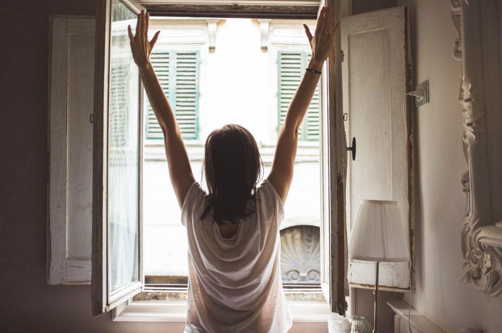Frau streckt sich vor Fenster