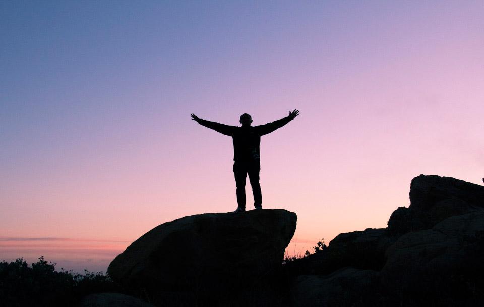 Mann steht auf Felsen vor Sonnenuntergang