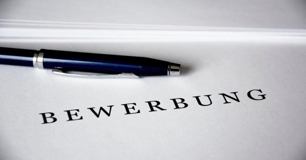 Bewerbungsschreiben mit Kugelschreiber auf Tisch