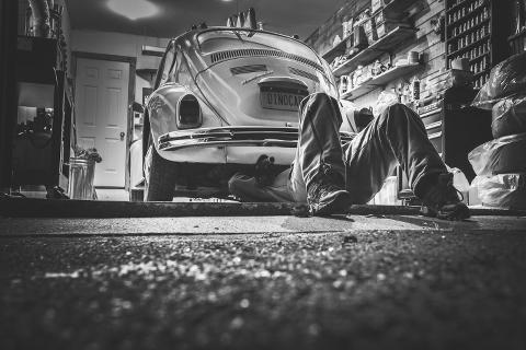Mechaniker liegt unter VW Käfer und betätigt sich handwerklich