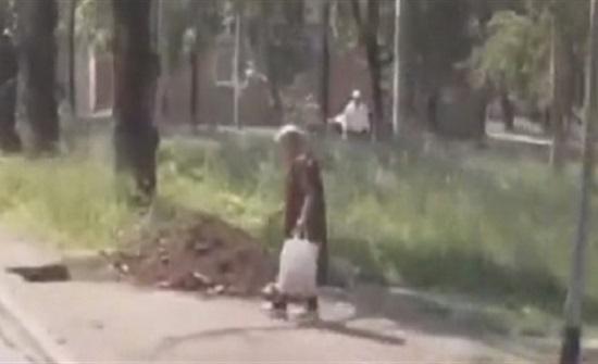 لحظة ابتلاع حفرة لامرأة على الطريق (فيديو)