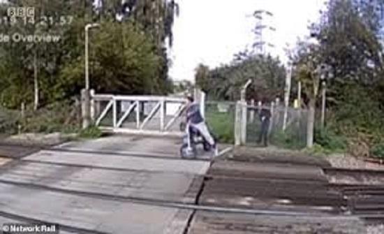راكب دراجة نارية ينجو من موت محقق أسفل قطار سريع (فيديو)