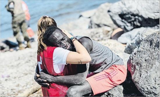 عناق إنساني بين متطوعة بالصليب الأحمر ومهاجر غير شرعي يثير الجدل
