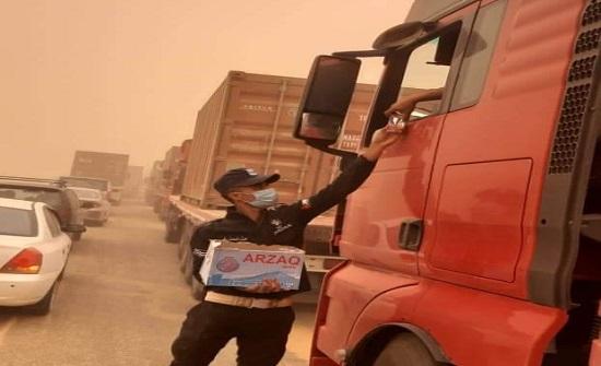 بالصور : نقطه شرطة توزع مياه على المركبات المتوقفة بسبب الغبار على الطريق الصحراوي