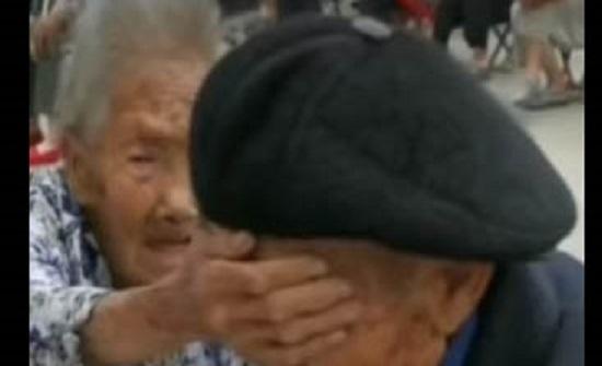 عجوز صينية تغطي عيني زوجها الخائف أثناء سحب دم منه لتهدئة أعصابه