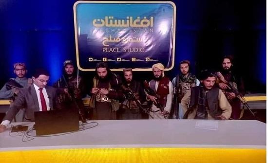 مذيع يجري حوارا مع قيادي بطالبان والسلاح فوق رأسه (شاهد)