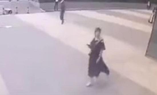 لحظة سقوط لوحة إعلانات من مبنى عال على رأس امرأة (فيديو)