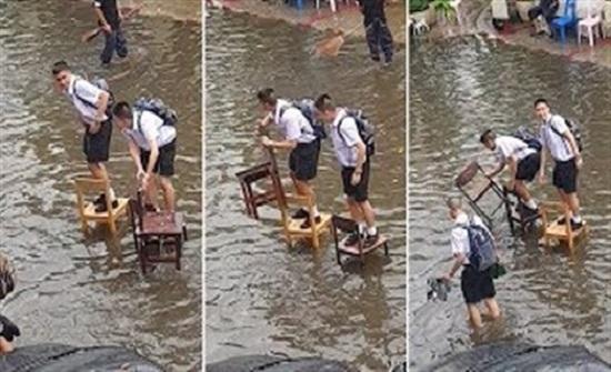 طلاب مدرسة يستخدمون كراسي خشبية لعبور طريق مغمور بالمياه (فيديو)
