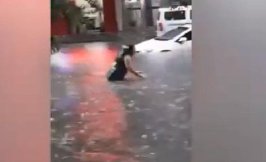 سيدة تسبح وسط الامطار