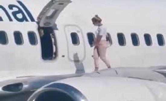 """""""كأنها تتجول على الكورنيش""""..  امرأة تقفز على جناح الطائرة - فيديو"""