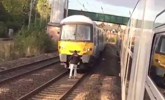 رجل يقف أمام قطار مهيأ للانطلاق في ألمانيا ليرغمه على انتظار زوجته